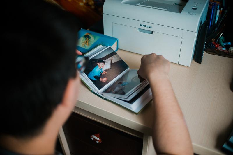 Артур достает детские альбомы: показывает фото, где он готовит. Рассказывает, как выглядят его первые палки для передвижения, находит фото с первогодняв школе.