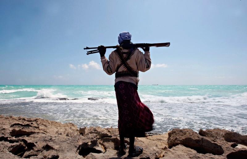 Пират смотрит на греческое грузовое судно MV Filitsa, захваченное и поставленное на якорь неподалеку от порта Хобьо на северо-восточном побережье Сомали, 7 января 2010 года. Фото: Mohamed Dahir / AFP / East News.