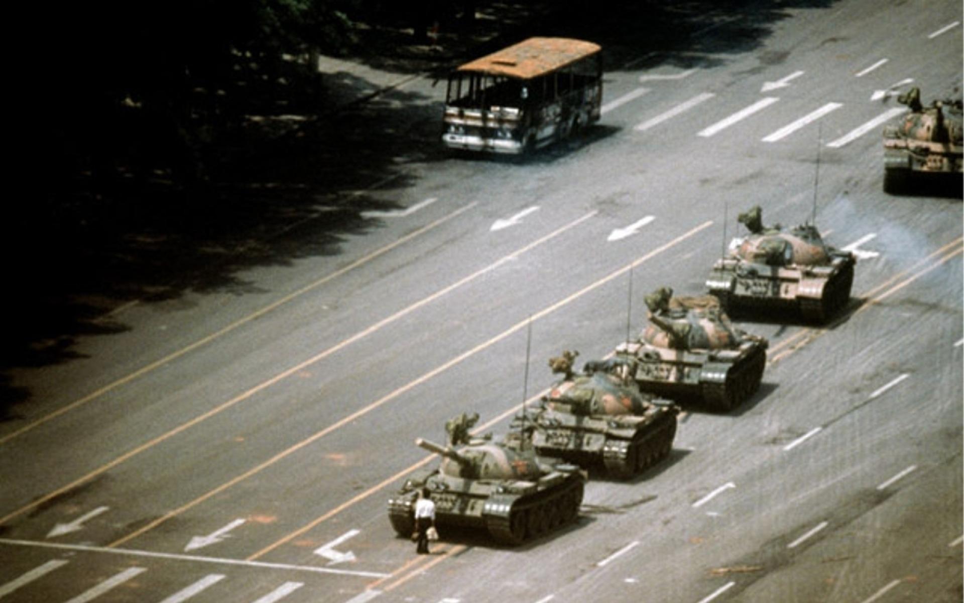 Блогер Антон Мотолько изучает разбитый асфальт, по которому идут танки. Фото: Джефф Вайденер