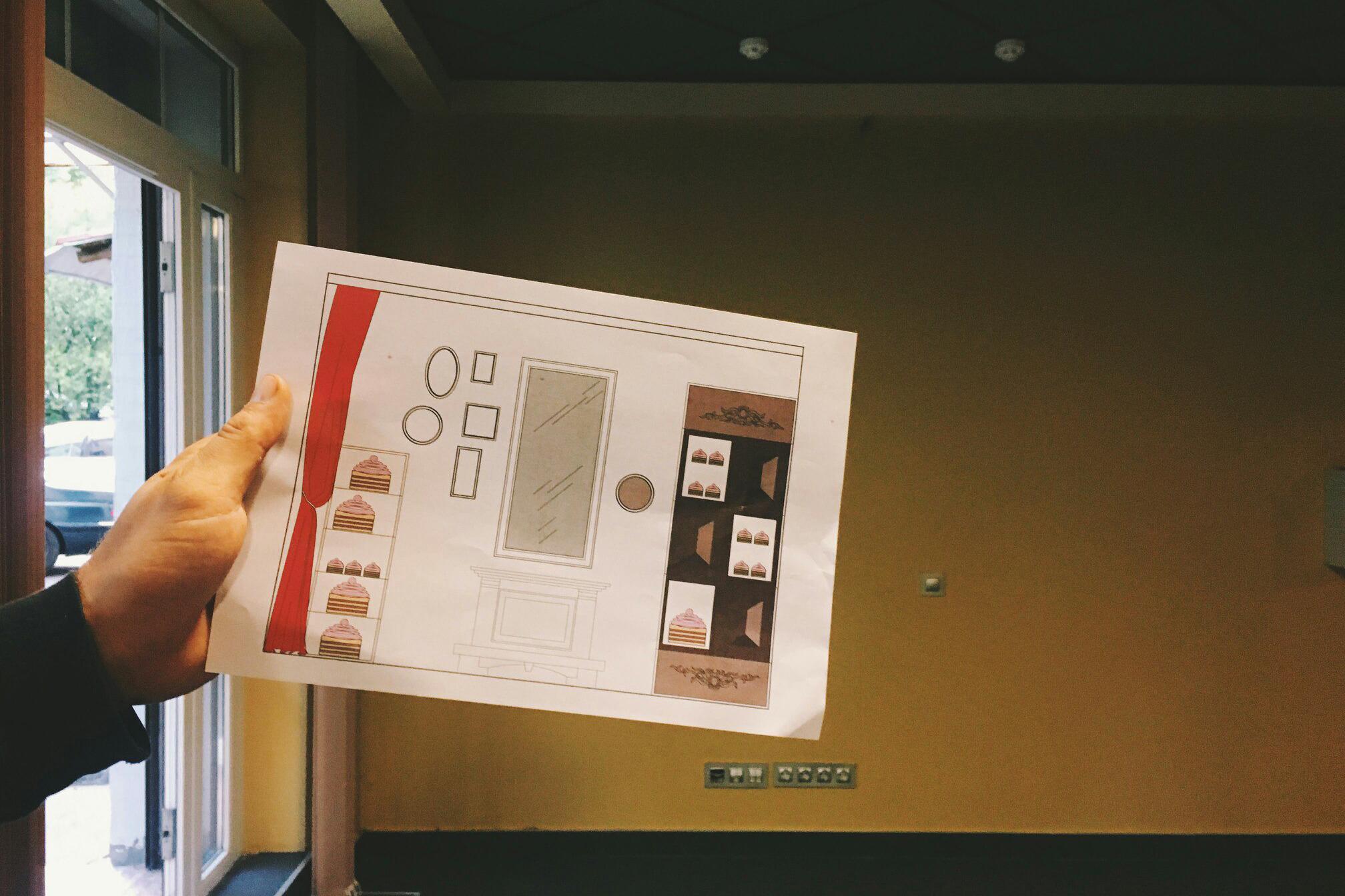 Евгений показывает макет дизайна на фоне той стены, которую предполагается преобразить
