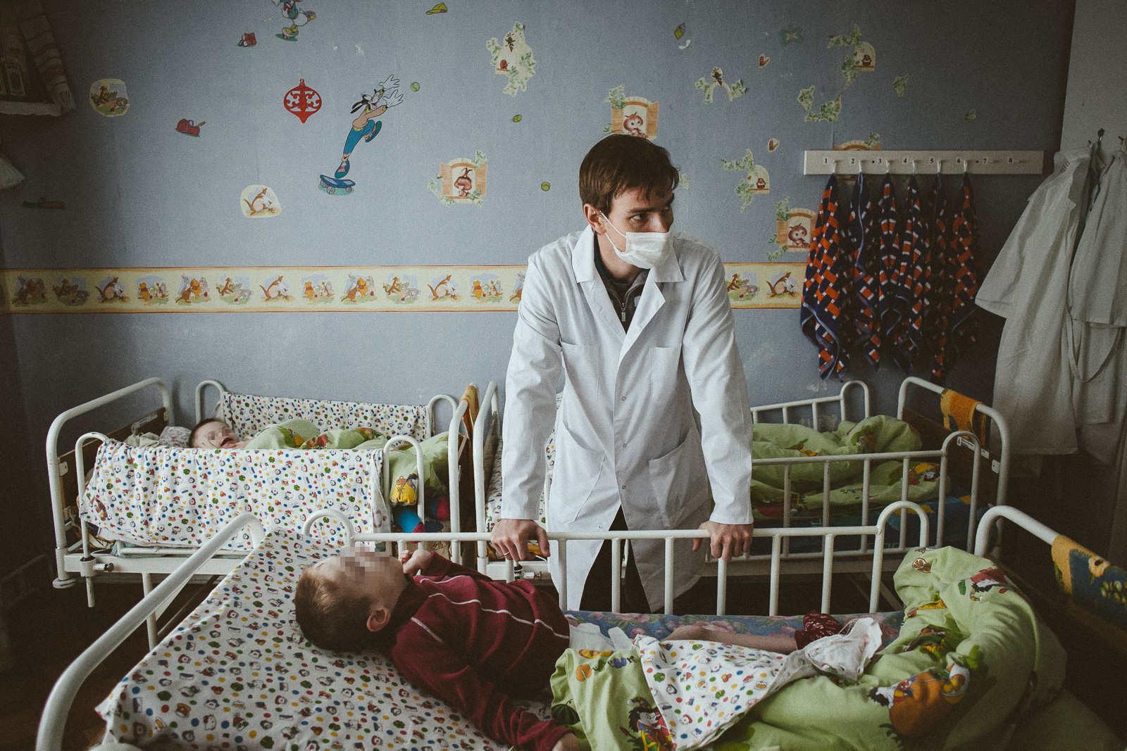 Врач интерната Алексей Момотов возле кровати ребенка. Фото: Александр Васюкович, Имена