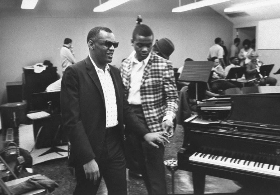 Помошник Вернон Троуп ведет Рея Чарльза к роялю в студии в Лос-Анджелес